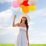 Mujer joven sonriente en gafas de sol con los globos Fotografía de archivo libre de regalías