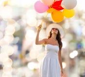 Mujer joven sonriente en gafas de sol con los globos Imagenes de archivo