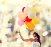 Mujer joven sonriente en gafas de sol con los globos Fotografía de archivo