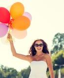 Mujer joven sonriente en gafas de sol con los globos Foto de archivo libre de regalías