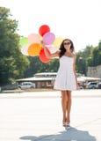 Mujer joven sonriente en gafas de sol con los globos Fotos de archivo libres de regalías