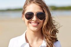 Mujer joven sonriente en gafas de sol en la playa Fotografía de archivo libre de regalías