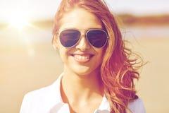 Mujer joven sonriente en gafas de sol en la playa Foto de archivo