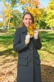 Mujer joven sonriente en Gray Coat Holding Leaves Fotos de archivo libres de regalías