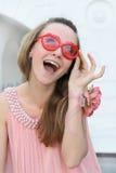 Mujer joven sonriente en la alineada rosada fotografía de archivo