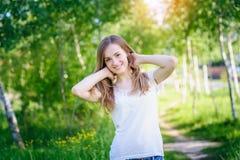 Mujer joven sonriente en la arboleda del abedul en primavera Fotos de archivo libres de regalías