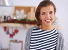 Mujer joven sonriente en la cocina, aislada encendido Fotos de archivo