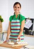 Mujer joven sonriente en la cocina, aislada encendido Imágenes de archivo libres de regalías