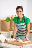 Mujer joven sonriente en la cocina, aislada encendido Foto de archivo libre de regalías