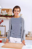 Mujer joven sonriente en la cocina, aislada encendido Imagen de archivo libre de regalías