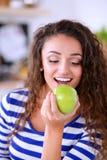 Mujer joven sonriente en la cocina en casa Mujer joven sonriente Imagen de archivo libre de regalías