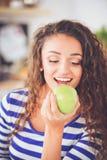 Mujer joven sonriente en la cocina en casa Mujer joven sonriente Fotografía de archivo libre de regalías
