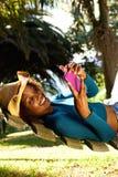 Mujer joven sonriente en la hamaca con el teléfono móvil Imagen de archivo