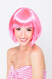 Mujer joven sonriente en la peluca rosada que presenta en el fondo blanco Fotos de archivo libres de regalías