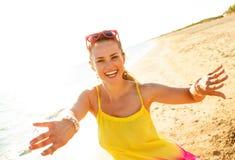 Mujer joven sonriente en la playa por la tarde que tiene tiempo de la diversión imágenes de archivo libres de regalías