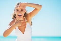 Mujer joven sonriente en la playa que enmarca con las manos Imágenes de archivo libres de regalías
