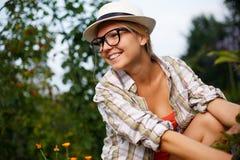 Mujer joven sonriente en los vidrios y el sombrero que descansan en jardín fotos de archivo libres de regalías
