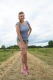 Mujer joven sonriente en pantalones cortos y camiseta que presenta en un fondo de la hierba y del cielo Imagen de archivo libre de regalías