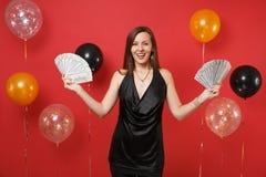 Mujer joven sonriente en poca celebración negra del vestido, celebrando porciones del paquete de dólares, dinero del efectivo en  fotos de archivo libres de regalías