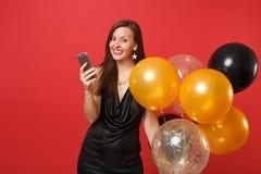 Mujer joven sonriente en poco vestido negro que sostiene los balones de aire usando el teléfono móvil mientras que celebra en bri imagenes de archivo