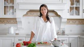 Mujer joven sonriente en rebanada que intenta de la camisa blanca de pepino orgánico fresco mientras que cocina la ensalada del v almacen de video