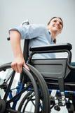Mujer joven sonriente en silla de ruedas Foto de archivo