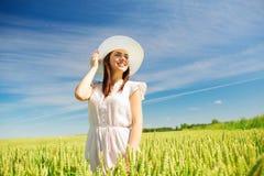 Mujer joven sonriente en sombrero de paja en campo de cereal Foto de archivo