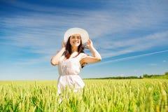 Mujer joven sonriente en sombrero de paja en campo de cereal Fotografía de archivo