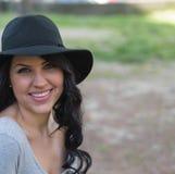 Mujer joven sonriente en sombrero negro Imagen de archivo