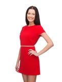 Mujer joven sonriente en vestido rojo Imagen de archivo libre de regalías