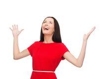 Mujer joven sonriente en vestido rojo con las manos para arriba Fotos de archivo