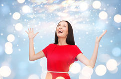 Mujer joven sonriente en vestido rojo con las manos para arriba Foto de archivo libre de regalías