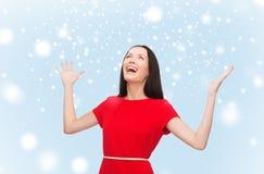 Mujer joven sonriente en vestido rojo con las manos para arriba Fotos de archivo libres de regalías