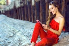 Mujer joven sonriente encantadora que se sienta en la playa en las pilas oxidadas viejas y que habla vía la conexión video en su  Imagen de archivo libre de regalías