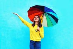 Mujer joven sonriente feliz con el paraguas colorido en el día del otoño que mira para arriba sobre fondo azul colorido Imagen de archivo libre de regalías