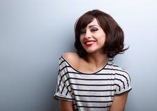 Mujer joven sonriente feliz con el pelo corto en azul Foto de archivo
