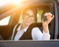 Mujer joven sonriente feliz con llave del coche Imagenes de archivo