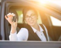 Mujer joven sonriente feliz con llave del coche Imagen de archivo libre de regalías