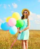 Mujer joven sonriente feliz con los globos coloridos de un aire que disfruta de un día de verano en el cielo azul del prado Imagen de archivo libre de regalías