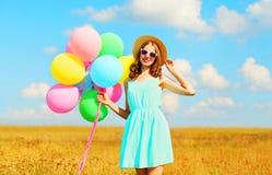 Mujer joven sonriente feliz con los globos coloridos de un aire que disfruta de un día de verano en fondo del cielo azul del camp Foto de archivo libre de regalías