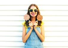 Mujer joven sonriente feliz con una piruleta en el palillo Foto de archivo libre de regalías