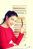 Mujer joven sonriente feliz del estudiante con los libros Foto de archivo libre de regalías