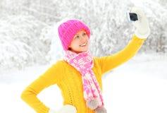 Mujer joven sonriente feliz del invierno de la moda que toma el autorretrato de la imagen en smartphone sobre los árboles nevosos Fotos de archivo