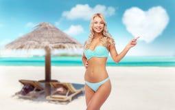 Mujer joven sonriente feliz en bikini en la playa foto de archivo