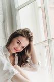 Mujer joven sonriente feliz en la camisa blanca del novio que se sienta por la ventana, en el fondo blanco Relajación por la maña Foto de archivo libre de regalías