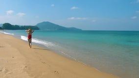 Mujer joven sonriente feliz en sombrero del sol y traje de baño rojo que camina en la playa a lo largo de la playa, vacaciones de almacen de metraje de vídeo