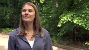Mujer joven sonriente feliz en sudaderas con capucha que da une vuelta en parque soleado el día del ` s del verano almacen de video