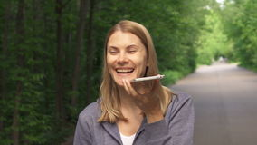 Mujer joven sonriente feliz en sudaderas con capucha que da une vuelta en parque soleado el día del ` s del verano y que habla en almacen de video