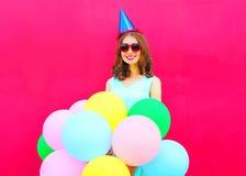 Mujer joven sonriente feliz en un casquillo del cumpleaños con los globos coloridos de un aire sobre fondo rosado Imagen de archivo libre de regalías