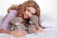 Mujer joven sonriente feliz hermosa con el oso de peluche en cama en h Imágenes de archivo libres de regalías